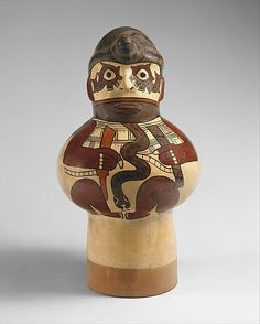 """28/ NAZCA - Drum, 45 cm. Ceramic drums were made in southern Peru at the turn of the 1st millennium. Among the most elaborate are those of Nasca style. Rich colors commonly used on Nasca ceramic vessels. Favored form = fat-bodied figure. Image is symbolically complex; snake, killer whale on each eye with tyical Nazca """"two-tone"""" color differentiation. Headband, hornlike projection on the forehead. Hair= serpents. http://www.museolarco.org/wp-content/uploads/2013/08/Tambor-Nazca.pdf"""