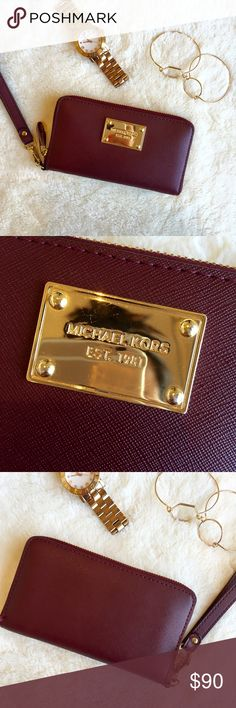 Michael Kors Leather Wristlet Authentic Michael Kors Wristlet from Macys. Burgundy color with gold details. Fits 3 credit cards. Comfortably fits an iPhone 5 in the middle designated pocket but I've also squeezed in my iPhone 6 on the side many times although it's a tight fit with my iPhone 6. Small minor scratches on the gold Michael Kors plate on the front but otherwise in good condition. No stains. Leather is in great condition! Michael Kors Accessories