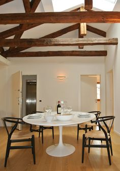 Soggiorno e sala da pranzo con arredi moderni e lineari. Soffitto con travi a vista #architettura #interni