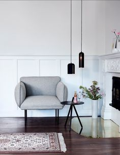 Dark wooden floors, grey lounge chair and brass