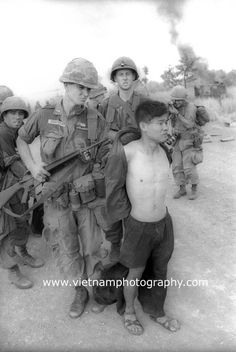Lt. Nick Terpstra, Artesia, Calif., leads a Viet Cong POW away from the battlefield. In the background an armored personnel carrier (APC) smolders. It hit a mine. The action took place July 9, 1966. The soldiers are from the 1st Battalion, 28th Infantry Regiment, 1st Infantry Division.