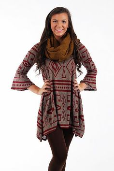 "Native Ways Dress, Burgundy $37.00 We are in love with this dress! The burgundy aztec print is very on trend this season, and the simple silhouette of this dress is spiced up with bell sleeves. This piece is lightweight enough to be layered as it gets colder!   Fits true to size. Britton is wearing a small.   From shoulder to hem:  Small - 32""  Medium - 33.5""  Large - 35""  XL - 36.5"""