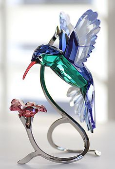 Swarovski Paradise Hummingbird, executed in full color crystal and fixed to a silver-tone metal display with a rose crystal flower.  Exquisite!