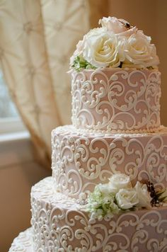 Piping on wedding cake with fresh flowers #weddingcakes