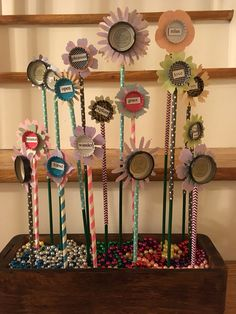 A paper window box garden made with bottle caps, popsicle sticks, magnetic poetry tiles, paper straws and ice tea caps with 6 Word Memoir quotes.
