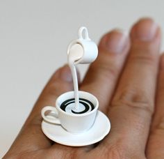 A super cute cup of Coffee with cream being poured!!!     It measures approx. 1.20 inch wide and 1.60 inch high and is on a silver plated adjustable bang that will fit most ring sizes.
