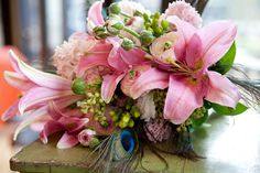 Creative inclusion of peacock feathers in a summertime bouquet from Buttercup: Cindy DeSau Photography.