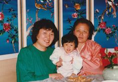 When I was young. With mom and grandmother on a family gathering day. Grandmother holds me with both hands. Mom wears green clothes and smiles.