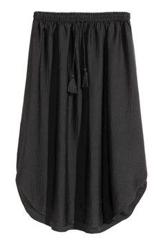 Jupe avec lien de serrage: Jupe de longueur genou en tissu vaporeux et brillant. Modèle avec élastique et lien de serrage terminé par pompons à la taille. Base arrondie.