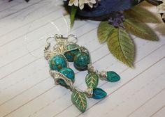 Wie eine Erdkugel präsentiert sich dieser türkis gefärbte Jaspis! Schön geschützt mit geflochtenem Silberdraht und abgerundet mit Blätteranhängern aus