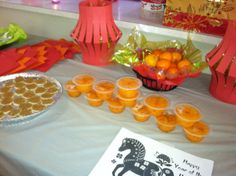 Chinese New Year Celebration food table: Cutie oranges and mandarins oranges in cups, rice crackers with peanut butter, lots of red and gold color. Tangerines and oranges are passed out freely during Chinese New Year as the words for tangerine & orange sound like luck & wealth, respectively.  Rice cakes: round shape of the cake represents family reunion or togetherness, the word gao implies prosperity and the sweetness symbolizes a sweet life.