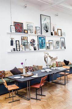 Zwarte open tafel op houten vloer, verschillende stoelen, kelim kussens en lijstenwand - love it