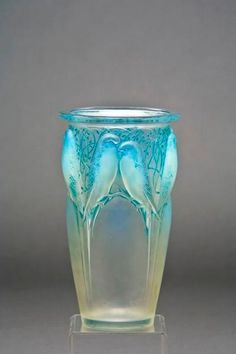 A Rene Lalique opalescent, frosted and stained glass 'Ceylan' vase, designed 1924, molded with budgerigars and stylized foliage, heightened with blue staining, wheel engraved R. Lalique France and etched N. 905
