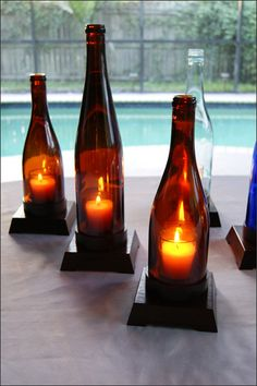 """Handcrafted Wooden Stand Trio Set of One Wine Bottle Candleholders - This is a beautiful decorative handcrafted wooden stand trio wine bottle candleholder set made with three 750 ml repurposed wine bottles. The colors of the glass add an ambiance great for an indoor table centerpiece, mantle display, wine bar, or a patio or porch area. The bottles sit on a 3/4"""" (+/-) wood base. Each bottle fits into its own individual stand. We handcraft our wood base."""