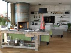 We designed a full height Cylindrical Fireplace for the main Sitting Room, clad in patinated sheets of copper with riveted joints, to echo the large external copper soffit that frames the front of the thatched roof and creates the dramatic silhouette of the structure, as seen from the water.