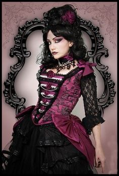 Steampunk/Victorian fashion style. Classic elements of the Victorian Era with the over-sized black ornate frame in the background.  A beautiful splash of vibrant magenta adds to the classic corsetted bodice, brocade fabrics, lace, ruffles with fancy trim, bussels & hoop skirts, choker necklaces with jewel trim & so much more.
