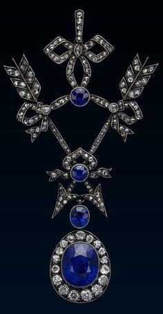 A Belle Epoque Sapphire and Diamond Pendant by Fabergé, 1910. Platinum millegrain and diamond pendant composed of two arrows tied at the base and top of the shafts by lover's knots, the ribbons highlighted by three collet set sapphires. Suspending a detachable pendant set with a larger sapphire, surrounded by diamonds. Work master, Albert Holmstorm. #Faberge #BelleÉpoque #pendant