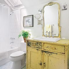 The Wicker House: bathroom - I love every single thing about this bathroom!  Love the distressed yellow, the tile, the skylight, the accordian mirror, the frog print!  Move in ready for me!