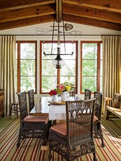 With three walls of windows (hello, views!), exposed rafters, and indoor-outdoor wicker seating, the home's eating space feels like an enclosed porch. This dining room certainly brings the outdoors in.