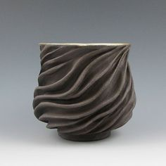 Hot beverages - the deep ridges keep hands from getting burnt without a handle. Hand thrown thick stoneware that is then individually carved