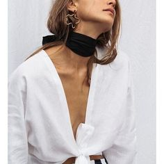 Neck scarf, tie detail white blouse, abstract shape earrings.
