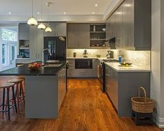 Appliances: Gray Cabinetry With Black Appliances. black kitchen appliances. black gas stove. black oven. black refrigerator. black countertop. gray kitchen cabinet. gray kitchen island. wooden barstools. white pendant light. wood flooring. wicker hamper.
