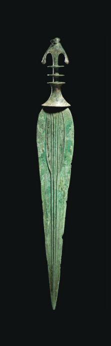 A LURISTAN BRONZE SWORD CIRCA 9TH-7TH CENTURY B.C. The tapering blade modelled with three ribs, each splitting in two towards the hilt, the waisted elliptical guard surmounted by two discs, the crescentic bifurcated pommel with notched finials 22 in. (55.9 cm.) long