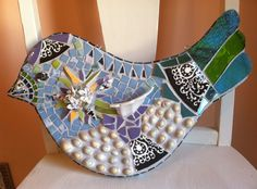 "Pretty blue and white 3D mosaic bird. By 'Sharondipity"". Tile, stained glass, shells, broken China, and grouted."