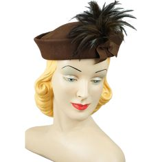 1950's brown felt pillbox hat.  Low indented crown with front side cluster of brown feathers held in place with brown grosgrain ribbon. Interior is