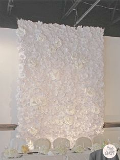 The Little Canopy's signature handmade paper flower wedding backdrop. The wall is 9 feet wide by 18 feet tall, and has about 600 handmade paper flowers on a fabric.