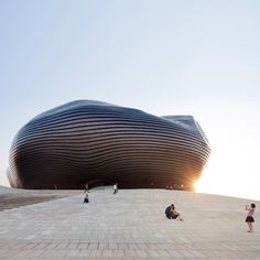 Ordos Museum by MAD: MAD envisioned a mysterious abstract form capable of fostering an alternate, timeless development of Chinese tradition and future. Whilst the surface of this shape functions as a metal container critical to protect the interior from the harsh winters and frequent sand storms of the region, metaphorically this external layer operates as a shield protecting the precious culture and history of the city from the unknown growth of the city.