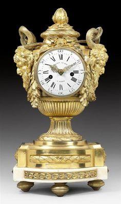 """VASENPENDULE """"AUX MASCARONS"""", Louis XVI, das Modell von R. OSMOND (Robert Osmond, Meister 1746), das Zifferblatt und Werk sign. JULIEN LE ROY A PARIS (Julien II Le Roy, Meister 1713), Paris um 1780. Bronze matt- und glanzvergoldet sowie """"Carrara""""-Marmor. Vasenförmiges Gehäuse mit markanten Satyr-Maskaronen und Schlangenhenkeln, Blütenknauf und konischem Rundfuss, auf gestuftem Bastionssockel mit Kreiselfüssen."""