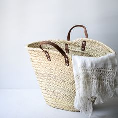 """Channel your inner european with this classic and timeless French flat leather handle market basket. Perfect for stocking up on your favourite farmer's market goodies or for packing up a killer picnic! Also great in the home to store blankets, books, toys, wool and even firewood. Handwoven in Morocco using dried palm leaves and finished with a genuine leather handle.Handwoven in MoroccoApproximately Long 20"""" x Wide 11"""" x 13"""" High"""