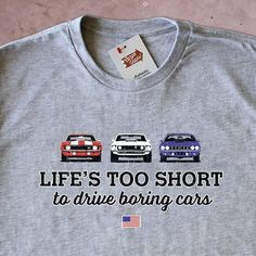 "This edition of the ""Life's Too Short to Drive Boring Cars"" shirt features a lineup of iconic British cars. The Austin-Healey 100M, the Aston Martin DB4, and the celebrated Jaguar E-Type. • Supremely"