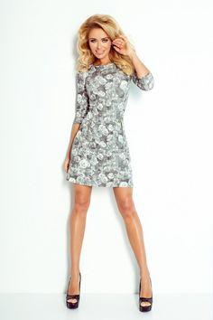 Niezwykle kobieca sukienka o kroju trapezowym, z klasycznie wszywanymi rękawami o długości 3/4, uszyta z przyjemnej w dotyku wzorzystej tkaniny z nadrukiem w róże. Model został zaprojektowany z dwoma kieszonkami na przodzie, zamykanymi na zamek błyskawiczny. #sukienka #dzienna #kobieta #moda #trendy #biel #czerń