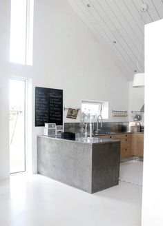 Lovely kitchen - grey slab of concrete, with white, black and wood detail