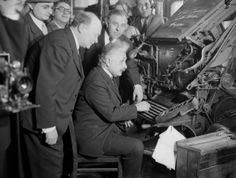 """Einstein is shown at the keyboard of a linotype machine in the composing room of the Jewish Daily Bulletin, NY, January 15, 1933 as he participated in the inauguration ceremony of the newspaper's 1st tabloid edition  its circulation to newsstands. His appearance was in the nature of a """"stunt"""" and he obligingly posed for pictures making a pretense of pressing the keys, but setting not one letter of type. Looking on are Herman Bernstein, left, editor, and Jacob Landau, publisher."""