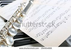 Flute and piano with music sheet close up - stock photo