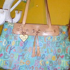 Dooney & Burke doodle bag Light blue, Multi colored doodle handbag, Reposh...ink pen marks shown in pics, slight wear on the corners. Good condition. Offers and trades are welcome. Dooney & Bourke Bags Shoulder Bags