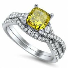 Cushion Cut Fancy Yellow Diamond Engagement Ring Bridal Set - One of the most elegant wedding sets we've seen on the market comes this 18k White Gold Cushion Cut Fancy Yellow Diamond Engagement Ring Bridal Set in a Pave & Prong setting with a Yellow Cushion cut center stone & White Round accent stones on the shank & band. This Cushion Cut Fancy Yellow engagement set comes with an SI1,VS1 & VS2 in clarity & the weight is equal to 1.45 carats. The diamonds are 100% natural…