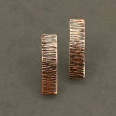 Little copper bars were hammered with horizontal lines for an interesting texture. Bars: Copper that has been hammered, curved slightly, and oxidized. Approximately 1 inch long and 1/4 inch wide. Posts: Sterling silver, 7/16 inch long. Sterling earring backs as shown in the