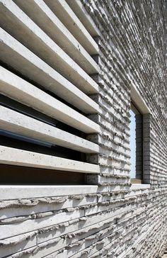 Dintells prefabricats de formigó com una reinterpretació de les antigues muralles. El relleu de la beurada reforça el seu caràcter aspre.