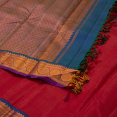 """The """"#Red"""" #handwoven #Kanjivaram #Silk #sari from Kanakavalli is set off by a orange motifs border on either side. Attractive circular and floral motifs adorn the blue pallu. The border is repeated on the blue blouse that completes the sari."""