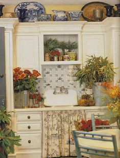 French Country Mudroom by Charlotte Moss - cream cabinets with delft tile backsplash and toile skirted sink