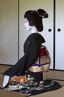 """Profile of geisha Kimiha from Miyagawacho, wearing a formal black kimono (tomesode) and a Shimada-styled nihongami wig. Her obi is tied in the """"taiko"""" (drum) style. All these are details which clearly distinguish her from a maiko (an apprentice)."""