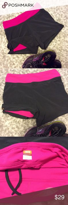 Lucy Brand Run Shorts Size Small. Outer front pockets and hidden key pocket. Inner leggings pink, outer shell dark gray, almost black. Drawstring.  High end athletic wear. Lucy Shorts