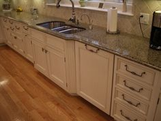 White cabinets, kitchen cabinets, undermount sink, stainless steel sink, dishwasher, dishwasher panel, full inset, angled sink, fluted columns, hardwood floors, granite, green countertops, pullout faucet, tile backsplash, angled tile