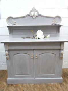 A solid Mahogany Chiffonier hand painted by TR in a blend of French Linen and Paloma, then further detailed with a white wash. The carved detailing has been gil