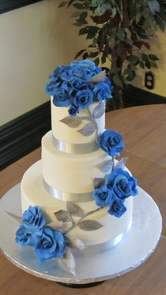 Sapphire roses and silver leaves. - Lemon rasp cake, iced with white choc ganache, MFF. Sapphire blue gumpaste roses, silver leaves