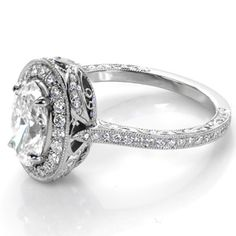 A meeting of elegant and vintage, this unique Knox Jewelers engagement ring features a haloed 1.20ct oval cut diamond atop a petite micro pavé band. Filigree, hand engraving and surprise marquise diamonds make this  a one-of-a-kind ring.